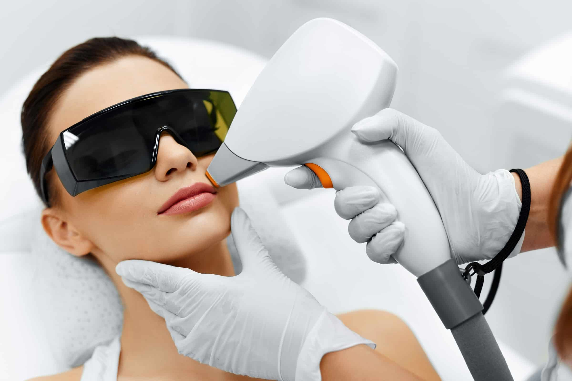 Laser hair removal treatment being performed on a woman's top lip