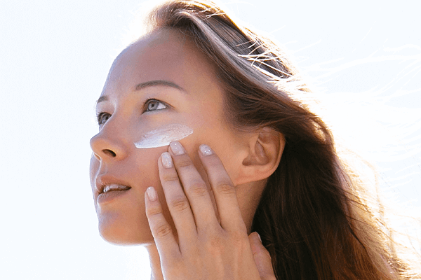 A women putting on sunscreen protection
